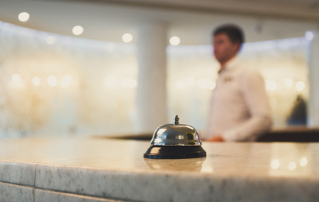 Photo pour Hotel accommodation call bell on reception desk, contemporary interior, blurred man guest on background, copy space - image libre de droit
