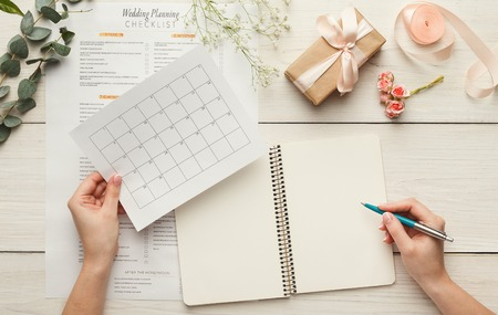 Photo pour Wedding background with checklist and calendar. Female hands arranging marriage, filling in planners on white wooden table with lots of tender bridal stuff, top view - image libre de droit