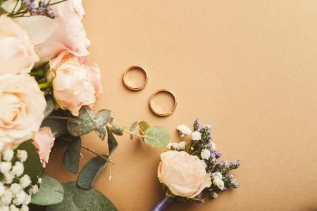 Foto de Wedding bride bouquet, floral corsage and two gold rings on beige background with copy space, top view. Preparation, wedding, advertisement, romance concept - Imagen libre de derechos