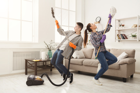 Foto de Young couple cleaning home, playing with mop and vacuum cleaner, having fun in living-room. Housekeeping and home cleaning concept - Imagen libre de derechos