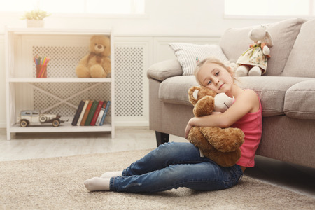 Photo pour Cute happy little casual girl embracing teddy bear. Pretty kid at home, sitting on the floor near sofa with her favourite toy, copy space - image libre de droit