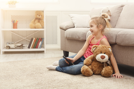 Foto de Little casual girl watching tv at home. Female kid sitting on the floor carpet with her toy friend teddy bear, holding remote and switching channels - Imagen libre de derechos