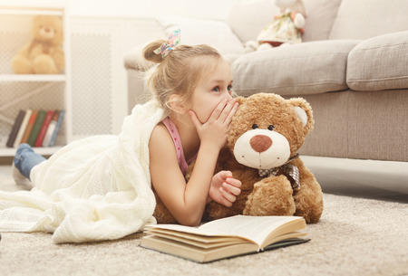 Photo pour Cute happy little casual girl embracing teddy bear, reading book and sharing secrets with her favorite toy friend. Pretty kid at home, lying on the floor near sofa - image libre de droit