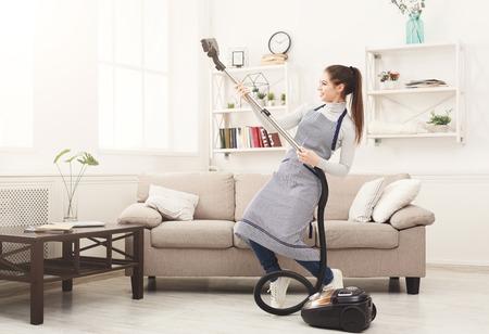 Foto de Happy woman cleaning home, dancing with vacuum cleaner and having fun, copy space. Housework, chores concept - Imagen libre de derechos