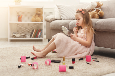 Foto de Cute little girl trying her mom`s cosmetics. Pretty kid sitting on the floor carpet among lots of beauty products. Small fashionista doing make up - Imagen libre de derechos