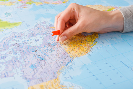 Foto de Travelling background. Female hand tackling country with flag-pin on the map. Tourism and vacation concept - Imagen libre de derechos