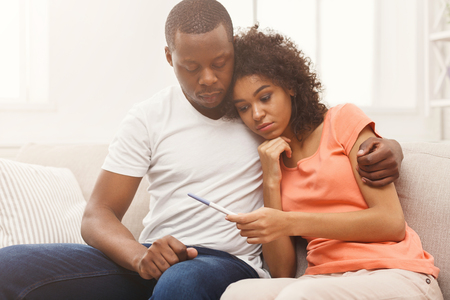 Photo for Sad african-american couple after negative pregnancy test result, sitting on couch at home, copy space - Royalty Free Image