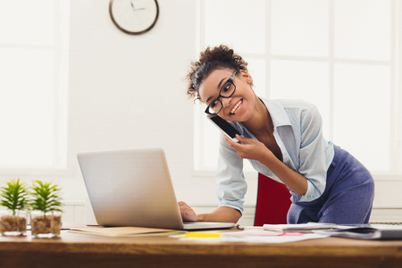 Foto de Happy african-american business woman talking on mobile at office. Young female manager consulting on phone, using laptop at working place, copy space - Imagen libre de derechos