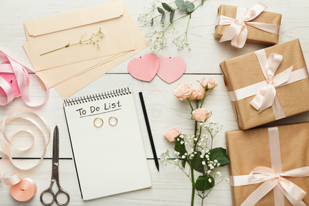 Foto de Wedding background with checklist. Paper planner and craft envelopes on white wooden table with lots of tender bridal stuff, top view - Imagen libre de derechos
