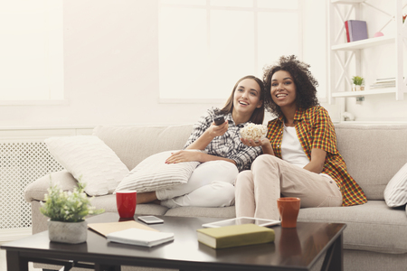 Foto de Smiling female friends relaxing and watching TV at home, eating popcorn, having rest after hard week, copy space - Imagen libre de derechos