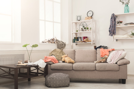 Foto de Sofa in messy living room with many stack of clothes. Disorder and mess at home, copy space - Imagen libre de derechos