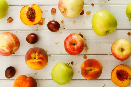 Photo for Healthy seasonal fruits background. Lots of ripe apples, peaches and plums, oat flakes and raisins on white wooden table top view, pattern, autumn harvest concept - Royalty Free Image