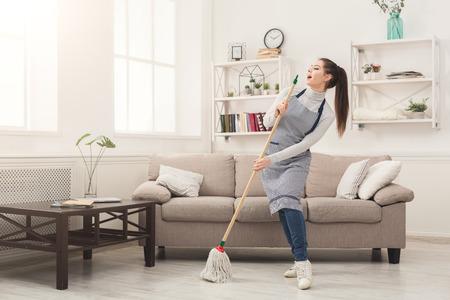 Foto de Happy woman in uniform cleaning home, singing at mop like at microphone and having fun, copy space. Housework, chores concept - Imagen libre de derechos