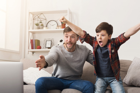 Photo pour Father and son watching football on TV at home. Emotional man and little boy cheering their favorite team, family enthusiasm, copy space - image libre de droit