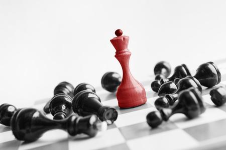 Foto de White chess queen beats blacks on chessboard over white background. Win and success concept, copy space - Imagen libre de derechos