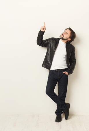 Photo for Confident casual man pointing up. Guy in leather jacket over white studio background. Advertising poster, copy space - Royalty Free Image