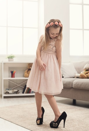 Photo pour Pretty little girl in moms shoes. Small fashionista trying on high heels at home, copy space - image libre de droit