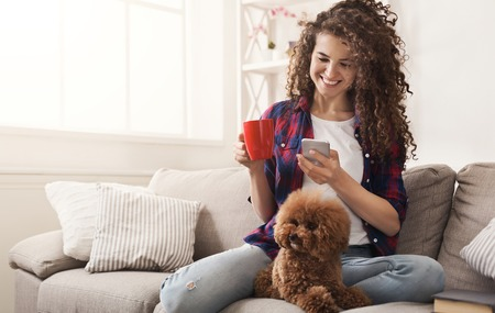 Photo pour Happy girl with smartphone and dog at home. Curly woman messaging online on couch with her puppy, copy space - image libre de droit
