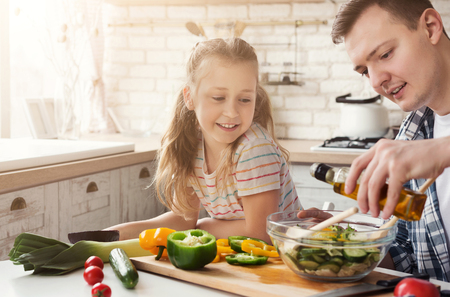 Foto de Positive dad and little daughter cooking in kitchen at home. Man teaching girl to add salad dressing, copy space - Imagen libre de derechos