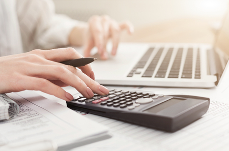 Photo pour Business woman checking balance. Internal Revenue Service inspects document with laptop computer and calculator, copy space - image libre de droit