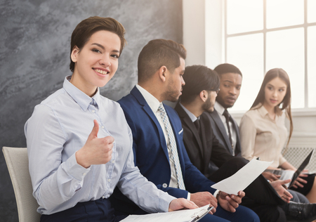Photo for Cheerful woman showing thumb up, multiethnic people waiting in queue. preparing for job interview and reading cv, copy space - Royalty Free Image
