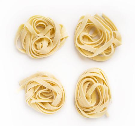 Foto de Raw tagliatelle nests isolated on white background. Traditional Italian pasta - Imagen libre de derechos