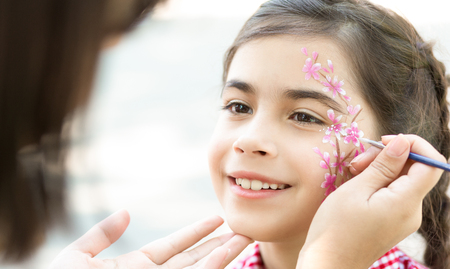 Photo for Children face painting. Little girl having fun, making creative floral design outdoors, copy space - Royalty Free Image