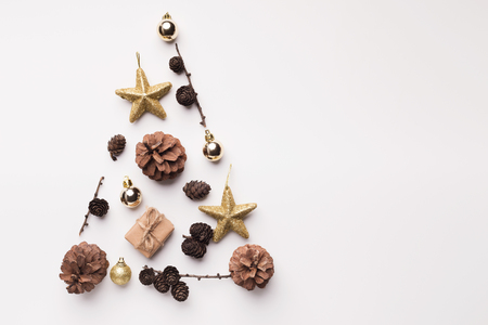 Photo pour Christmas tree made from golden stars and cones on white background - image libre de droit