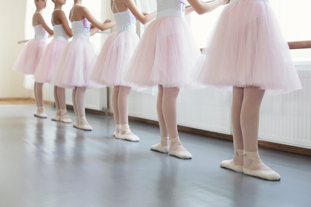 Photo for Young ballerinas in basic position. Ballet dancers standing near ballet barre - Royalty Free Image