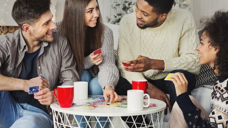 Photo pour Multiracial friends having fun and playing game of cards UNO against christmas tree - image libre de droit
