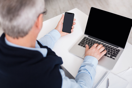 Foto de Mature man using laptop and smartphone with blank screen back view, copy space, mockup - Imagen libre de derechos