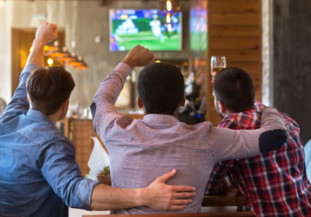Photo for Male friends watching football match on TV in sport bar, back view - Royalty Free Image