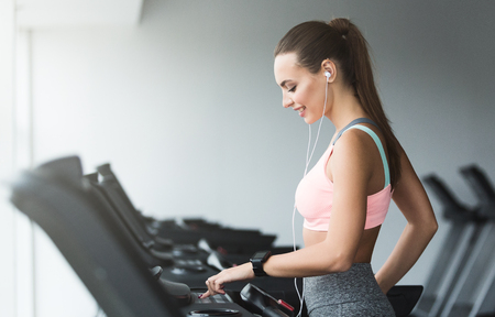 Foto per Woman adjusting speed on treadmill, doing cardio workout in sports club - Immagine Royalty Free