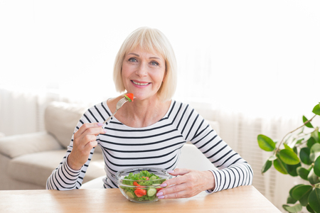 Photo pour Happy senior lady eating fresh green salad, having rest at home - image libre de droit