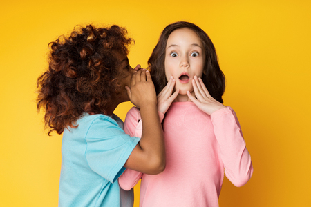 Photo for Girl telling secret to her friend, whispering in ear, yellow studio background - Royalty Free Image