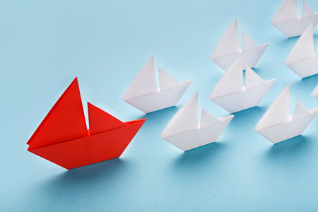 Photo pour Opinion Leader, influencer concept. One red boat leading small white ships on blue background - image libre de droit
