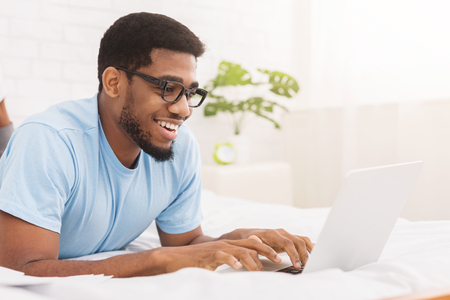 Photo for Black man blogger typing on laptop, chatting with followers, enjoying wireless internet in bed, copy space - Royalty Free Image