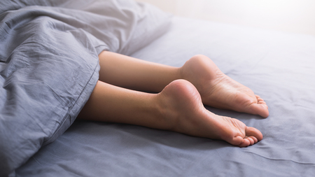 Foto de Beautiful female legs with smooth sole lying in bed under blanket, panorama, closeup - Imagen libre de derechos