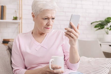 Photo for Myopia. Senior woman holding phone near face, trying to see message, free space - Royalty Free Image