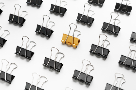 Photo for Mobbing, bullying and individuality. One yellow binder clip between black ones, closeup - Royalty Free Image