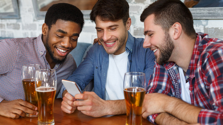 Photo pour Friends having fun. Men using smartphone and drinking beer in bar - image libre de droit