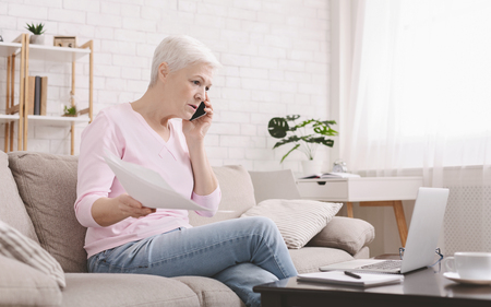 Foto de Angry senior woman talking on phone and working at home, looking at laptop and waving paper correspondence, sitting at home, free space - Imagen libre de derechos