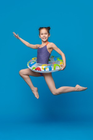 Foto de Happy child girl in swimsuit jumping with swimming ring on blue studio background - Imagen libre de derechos