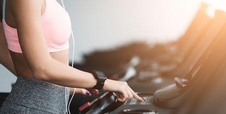 Photo for Adjusting speed. Woman training on treadmill, doing cardio workout in gym, crop - Royalty Free Image
