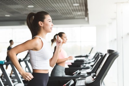 Foto per Asian girl working out on treadmill at the gym, side view, copy space - Immagine Royalty Free