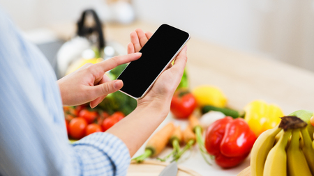 Photo pour Search Recipe. Woman Using Smartphone Preparing For Cooking Healthy Salad At Home - image libre de droit