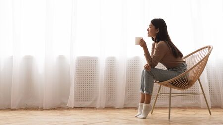 Photo pour Girl Enjoying Morning Coffee, Sitting In Armchair In Front Of Window, Side View - image libre de droit