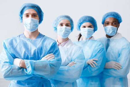 Photo for Surgeons Team Ready for Surgery. Practitioners Wearing Protective Uniforms, Caps And Masks - Royalty Free Image