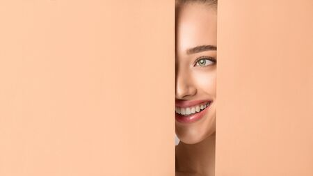 Photo pour Natural Beauty. Woman With Nude Makeup Peering Into Hole In Peach Paper, Copy Space - image libre de droit