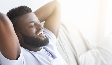 Photo for Happy morning. Satisfied black guy relaxing at home, lying with closed eyes, panorama with sun flare, free space - Royalty Free Image